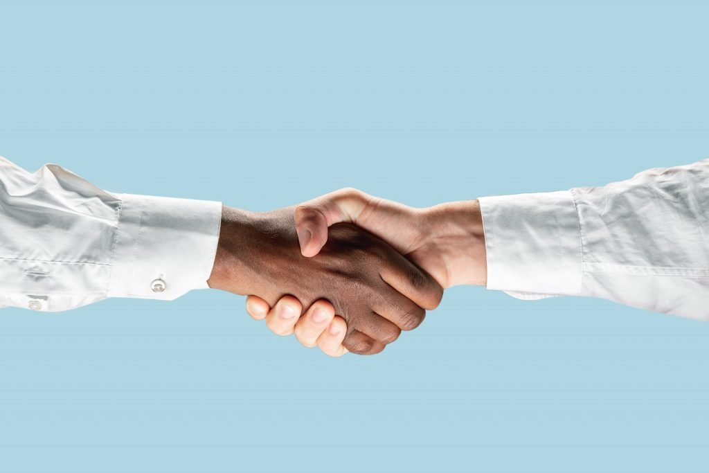 Two businessmen shaking hands, forearms and hands only. To illustrate reaching an agreement after negotiation.
